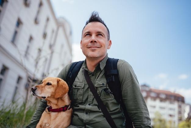 Mannen en zijn hond zittend op de straat in de stad