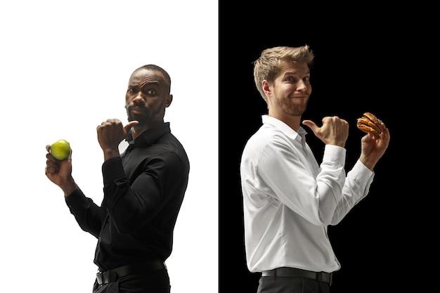 Mannen eten van een hamburger en vers fruit op een zwart-witte achtergrond. de blije afro en blanke mannen. het burger, snel, gezond en ongezond voedingsconcept