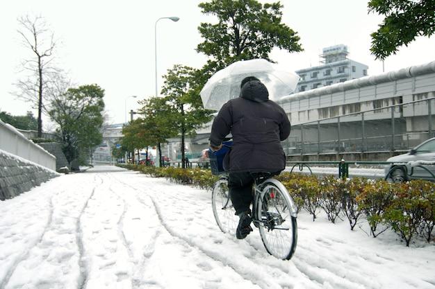 Mannen fietsen onder natte sneeuwval in de straten van tokio, japan, 2008