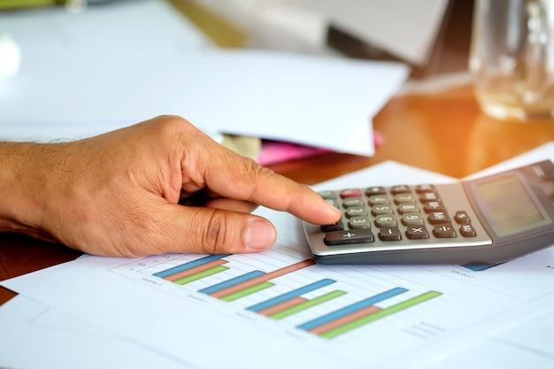 Mannen gebruiken een calculator om inkomensgegevens te analyseren.