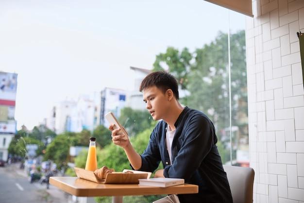 Mannen gebruiken telefoon op theetijd, met behulp van mobiele smartphone, internet van dingen levensstijl met draadloze communicatie en internet met smartphone.
