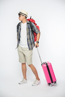 Mannen gekleed om te reizen, met bril en hoed, met tassen en bagage