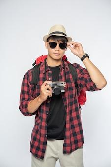 Mannen gekleed om te reizen, met bril en hoed, tas en camera