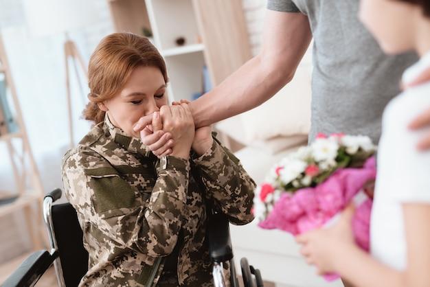 Mannen geven vrouw in rolstoelboeket bloemen.