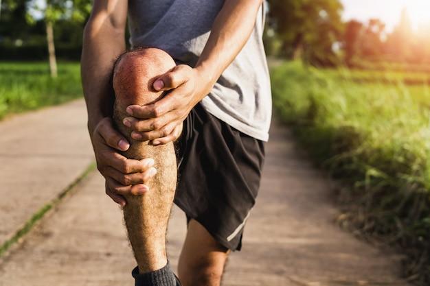 Mannen gewond door inspanning gebruik uw handen om uw knieën in het park te houden