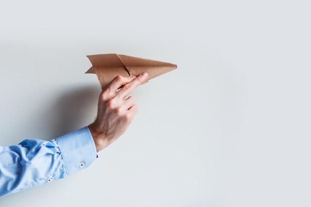 Mannen hand in een blauw shirt uniform lanceert een papieren vliegtuig.