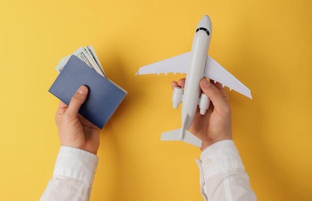 Mannen handen houden paspoort met geld vliegtuig gele achtergrond. bovenaanzicht