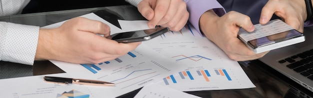 Mannen handen met rekenmachine en telefoon op documenten