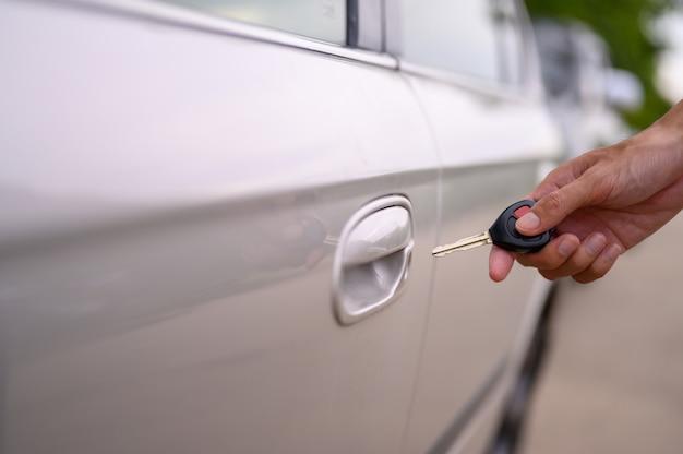 Mannen houden de autosleutels vast om de auto te openen.