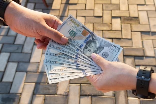 Mannen houden dollar biljet in hun handen voor een zakelijke uitwisseling