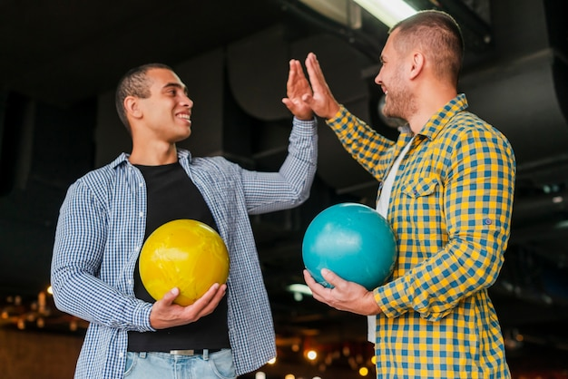Mannen houden van kleurrijke bowlingballen