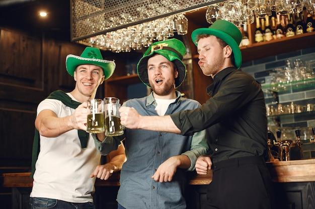 Mannen in groene hoeden. vrienden vieren st. patrick's day. viering in een pub.