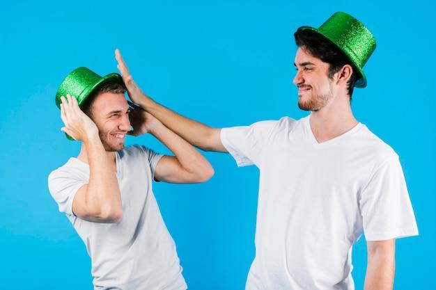 Mannen in groene prachtige hoeden plezier maken