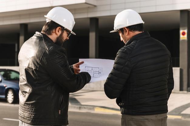 Mannen in helmen kijken naar plannen