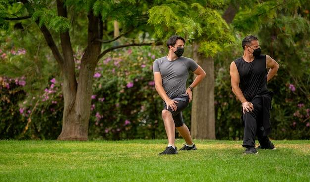 Mannen in het park met maskers die sportyoga doen en stretchen