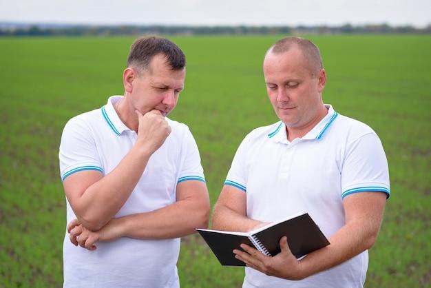 Mannen in het veld bestuderen aantekeningen in een notitieboekje