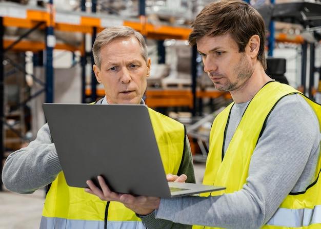 Mannen in magazijn die op laptop werkt