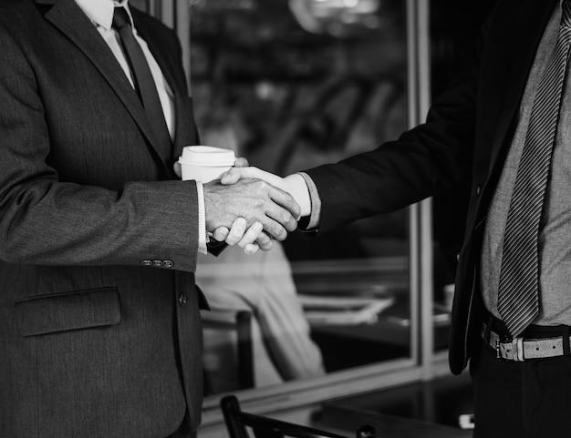 Mannen in pakken handen schudden