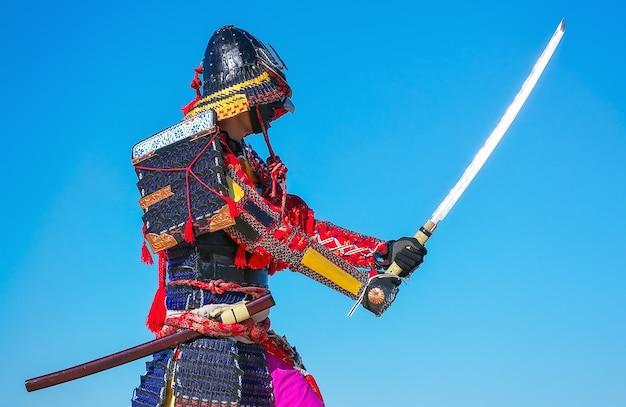Mannen in samoeraienpantser met zwaard op blauwe hemelachtergrond. origineel personage