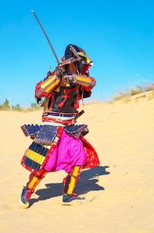 Mannen in samoeraipantser met zwaard dat op zand loopt