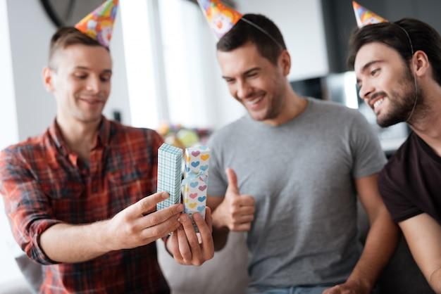 Mannen in verjaardagshoeden tonen elkaar cadeautjes.