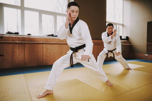Mannen in witte kleding en zwarte riemen trainen