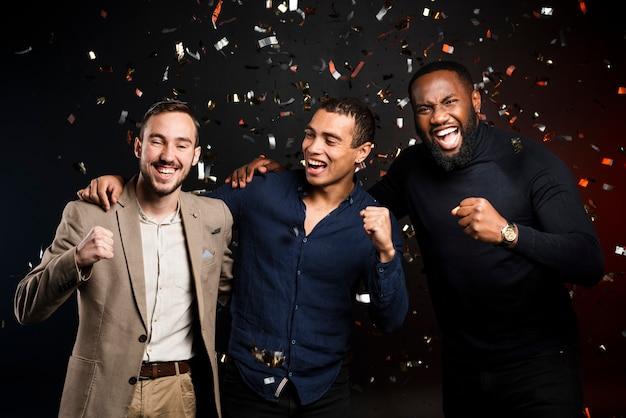 Mannen juichen omringd door confetti op feestje