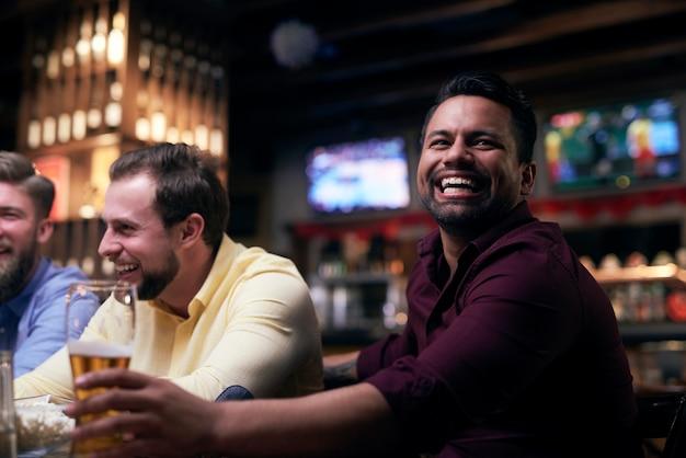 Mannen kijken naar amerikaans voetbal in de kroeg