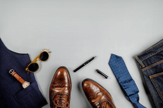 Mannen kleding concept. vintage-stijl. plat lag op lichtgrijze achtergrond. inclusief wingtips-kledingschoenen, handhorloge, pen, stropdas, jeans en zonnebril. stijlvolle mannen. bovenaanzicht