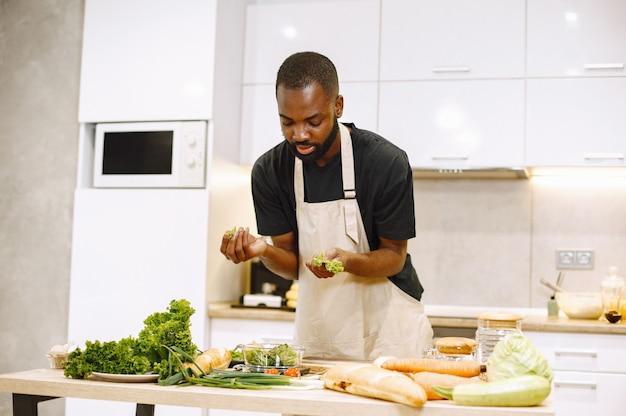 Mannen koken. afro-amerikaanse man die in een keuken verblijft. man in zwart t-shirt.