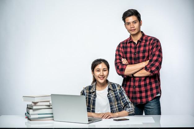 Mannen leren vrouwen op het werk met laptops te werken.