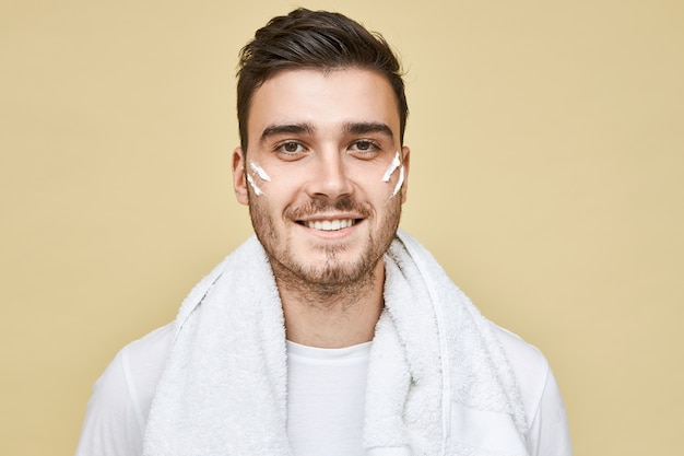 Mannen, levensstijl, schoonheid en huidverzorgingsconcept. foto van gelukkige jonge man met borstel poseren geïsoleerd met schuimstrepen op zijn wangen en badhanddoek om nek, gezicht wassen en stoppels scheren
