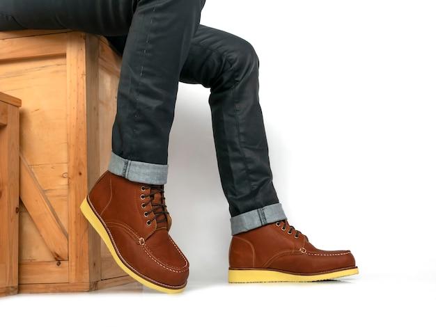 Mannen mannequin bruin laars leer en jeans zittend op houten doos