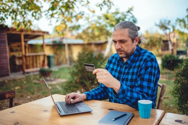 Mannen met creditcard op achtertuin patio