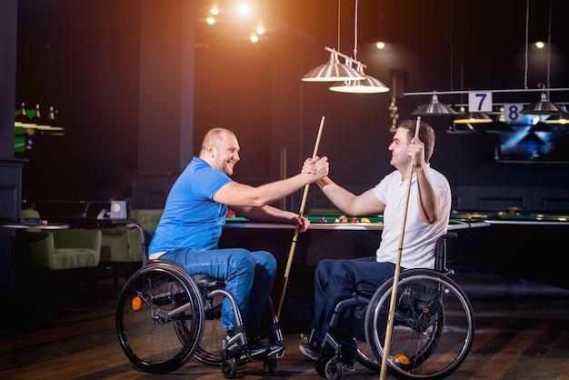 Mannen met een handicap in een rolstoel spelen biljart in de club
