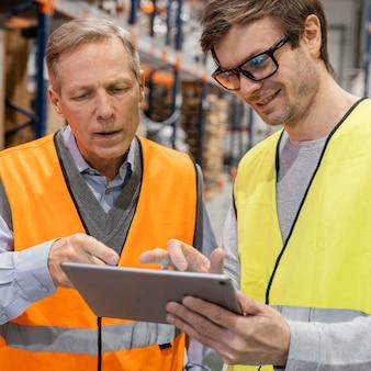 Mannen met een tablet die logistiek werkt