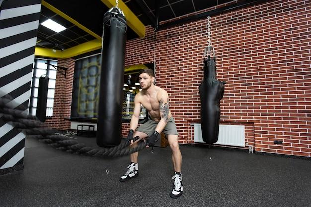 Mannen met gevechtstouw vechten touwen oefenen in de fitnessruimte. crossfit.