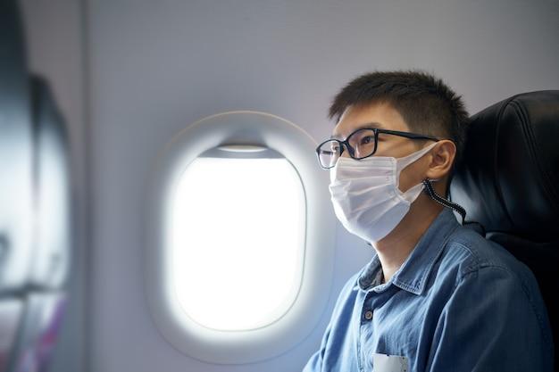 Mannen met gezichtsmasker reizen op de luchthaven, nieuwe levensstijl reizen na covid-19. social distancing en travel bubble concept.