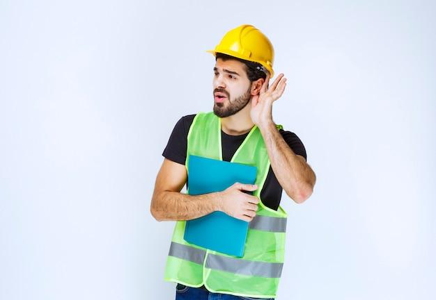 Mannen met helm die het oor openen om goed te horen.