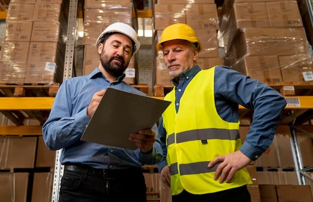 Mannen met helm werken in magazijn