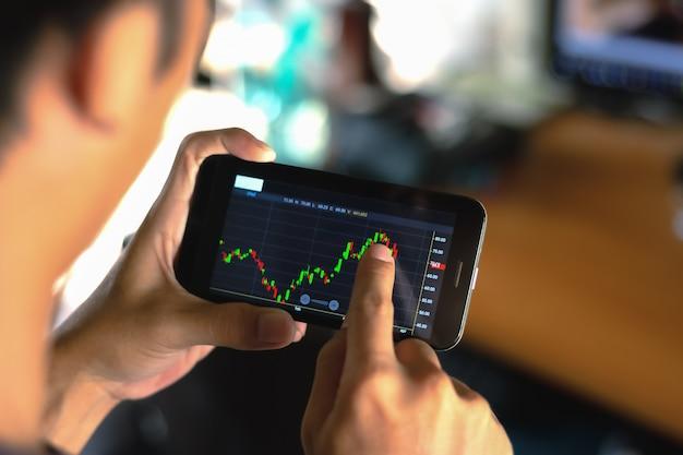 Mannen met mobiele telefoons om de aandelenmarkt te verhandelen.