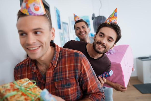 Mannen met verjaardagshoeden bereiden een verrassingsfeest voor.