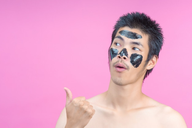 Mannen met zwarte cosmetica op hun gezichten en gebaren op een roze.