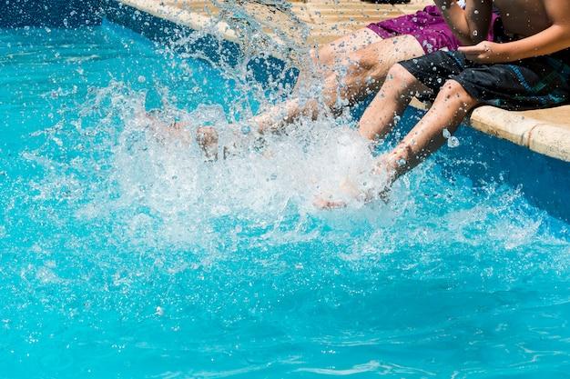 Mannen onder waterspetters aan de rand van het zwembad