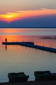 Mannen op ponton pier bij zonsondergang