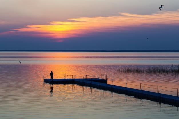 Mannen op pontonpijler bij zonsondergang