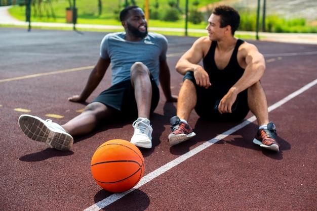 Mannen praten op het basketbalveld