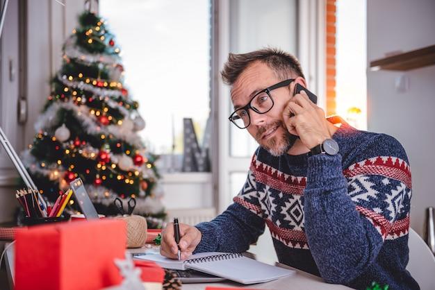 Mannen praten op slimme telefoon en notities schrijven