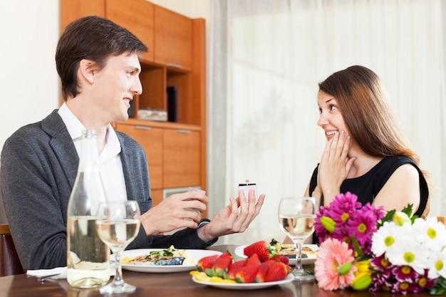 Mannen presenteren een geschenkdoos met sieraden binnen aan zijn vriendin