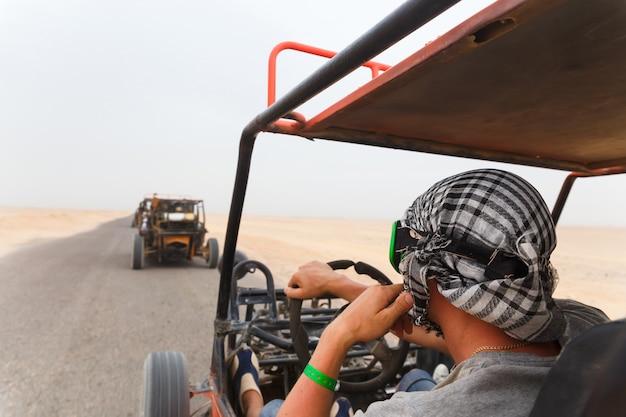 Mannen rijden auto met fouten in de woestijn